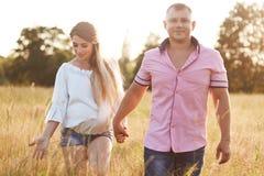 Счастливые молодые будущие родители имеют прогулку через зеленый луг, держат руки, насладитесь спокойной атмосферой, имейте счаст стоковое фото