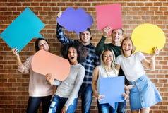 Счастливые молодые взрослые проводя пустой плакат думали copyspa пузырей Стоковое фото RF