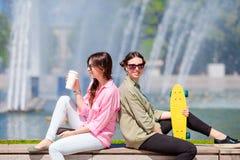 Счастливые молодые городские девушки в европейском городе Кавказская женщина имея потеху совместно outdoors Стоковые Фото
