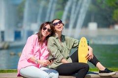 Счастливые молодые городские девушки в европейском городе Кавказская женщина имея потеху совместно outdoors Стоковое Фото