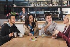 Счастливые молодые друзья выпивая кофе на кафе Стоковое Изображение RF