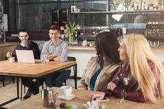 Счастливые молодые друзья выпивая кофе на кафе Стоковая Фотография RF