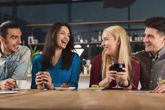 Счастливые молодые друзья выпивая кофе на кафе Стоковые Фотографии RF
