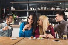 Счастливые молодые друзья выпивая кофе на кафе Стоковое Изображение