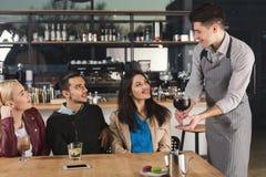 Счастливые молодые друзья выпивая кофе на кафе Стоковая Фотография
