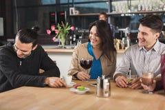 Счастливые молодые друзья выпивая кофе на кафе Стоковые Фото
