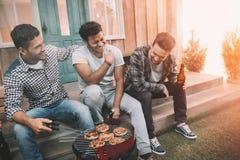 Счастливые молодые друзья выпивая пиво и имея потеху пока делающ стоковые изображения rf