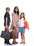 Счастливые молодые друзья стоя с хозяйственными сумками Стоковая Фотография RF