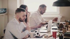 Счастливые молодые европейские бизнесмены сидят таблицей, работой вместе с компьтер-книжками в современном здоровом офисе, замедл сток-видео