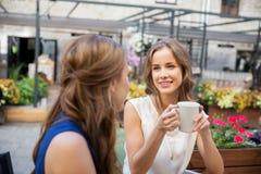 Счастливые молодые женщины выпивая кофе на внешнем кафе Стоковая Фотография