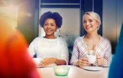 Счастливые молодые женщины выпивая чай или кофе на кафе Стоковое Изображение RF