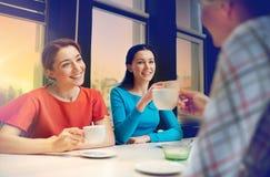 Счастливые молодые женщины выпивая чай или кофе на кафе Стоковые Фото