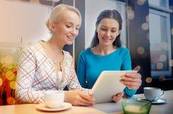 Счастливые молодые женщины выпивая чай или кофе на кафе Стоковая Фотография