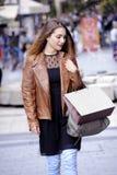 Счастливые молодые женщины идя и ходя по магазинам в городе Ультрамодный потребитель женщины смотря окна магазина Стоковое Фото