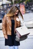 Счастливые молодые женщины идя и ходя по магазинам в городе Ультрамодный потребитель женщины смотря окна магазина Стоковые Фото