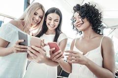 Счастливые молодые женщины показывая их smartphones друг к другу Стоковое фото RF