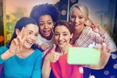 Счастливые молодые женщины принимая selfie с smartphone Стоковые Изображения RF