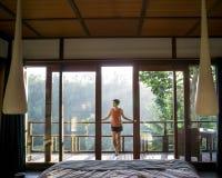Счастливые молодые женщины стоя около окна и чувствовать vibe утра, смотря красивый ландшафт после просыпать вверх в стоковые изображения