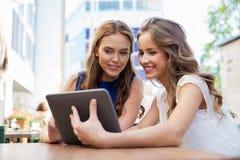 Счастливые молодые женщины с ПК таблетки на внешнем кафе Стоковые Изображения