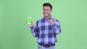 Счастливые молодые испанские телефон показа человека и давать большие пальцы руки вверх сток-видео