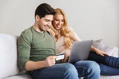 Счастливые молодые любящие пары сидя на софе держа кредитную карточку Стоковое Изображение