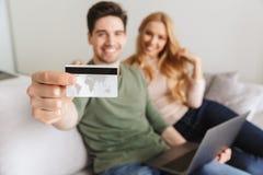 Счастливые молодые любящие пары сидя на софе держа кредитную карточку Стоковая Фотография RF