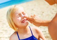 Счастливые молодые мать и дочь на пляже прикладывая SPF стоковое фото