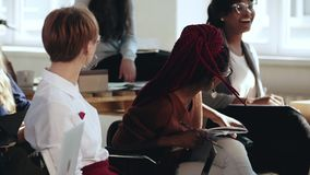 Счастливые молодые многонациональные женские работники деловой компании смеются слушать семинар на современном конференции офиса акции видеоматериалы