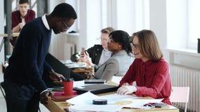 Счастливые молодые многонациональные разнообразные бизнесмены возраста, мужской менеджер и женщина босса, работают совместно на с акции видеоматериалы