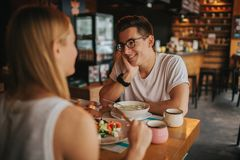 Счастливые молодые пары в влюбленности имея славную дату в баре или ресторане Они говоря некоторые рассказы о себе Стоковые Фото