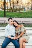 Счастливые молодые пары в влюбленности сидя на скамейке в парке и обнимать Стоковые Изображения