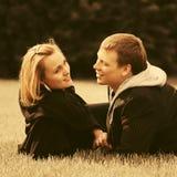 Счастливые молодые пары в любов лежа на траве в парке города стоковая фотография rf