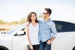 Счастливые молодые пары готовя автомобиль Стоковые Фото