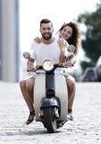 Счастливые молодые пары ехать самокат в городе на солнечный день Стоковая Фотография RF