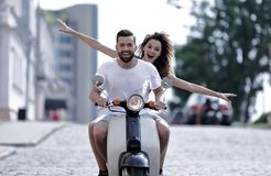 Счастливые молодые пары ехать самокат в городе на солнечный день Стоковые Изображения