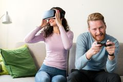 Счастливые молодые пары играя видеоигры с шлемофонами виртуальной реальности Стоковые Фотографии RF