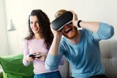 Счастливые молодые пары играя видеоигры с шлемофонами виртуальной реальности Стоковое Фото