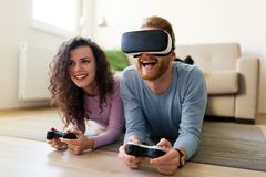 Счастливые молодые пары играя видеоигры с шлемофонами виртуальной реальности Стоковые Изображения RF