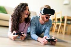 Счастливые молодые пары играя видеоигры с шлемофонами виртуальной реальности Стоковое Изображение RF