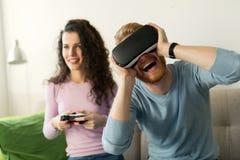 Счастливые молодые пары играя видеоигры с шлемофонами виртуальной реальности Стоковое фото RF
