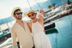 Счастливые молодые пары идя гаванью touristic морского курорта стоковые изображения