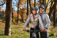 Счастливые молодые пары идя для велосипеда едут на день осени в парке Стоковые Изображения