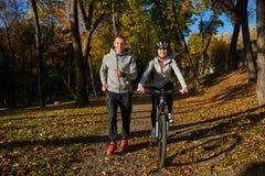 Счастливые молодые пары идя для велосипеда едут на день осени в парке Стоковые Фото