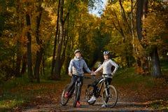 Счастливые молодые пары идя для велосипеда едут на день осени в парке Стоковые Фотографии RF