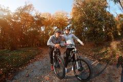 Счастливые молодые пары идя для велосипеда едут на день осени в парке, backlight Стоковая Фотография