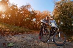 Счастливые молодые пары идя для велосипеда едут на день осени в парке, backlight Стоковое Изображение RF