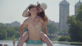 Счастливые молодые пары имея потеху на пляже Девушка сидя на задней части усмехаться парня Любовники наслаждаясь выходными близко видеоматериал