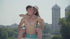Счастливые молодые пары имея потеху на пляже Девушка сидя на задней части усмехаться парня Любовники наслаждаясь выходными близко акции видеоматериалы