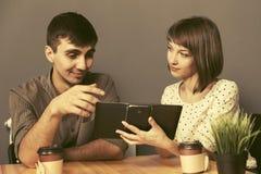 Счастливые молодые пары используя цифровой планшет сидя на таблице стоковое изображение rf