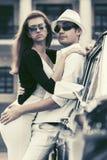 Счастливые молодые пары моды в влюбленности рядом с винтажным автомобилем Стоковые Фотографии RF